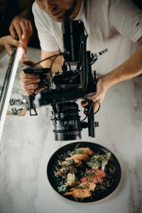 man using video camera pointing on food on plate